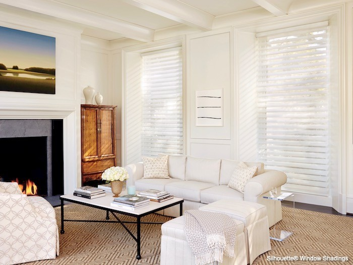 A living room with silky window shades and rougher carpet.